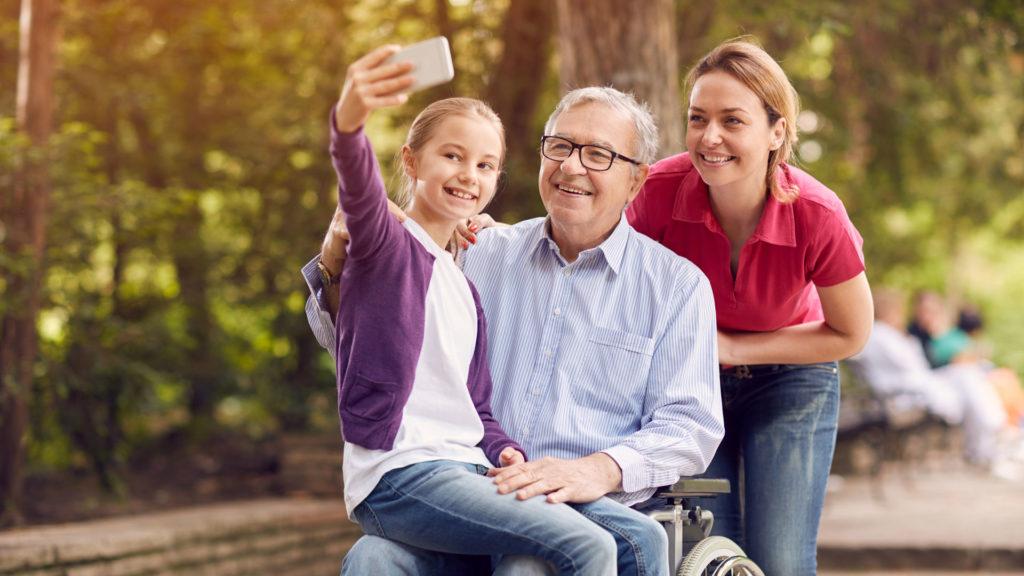 Une petite fille fait un selfie avec son père en fauteuil roulant, et sa mère