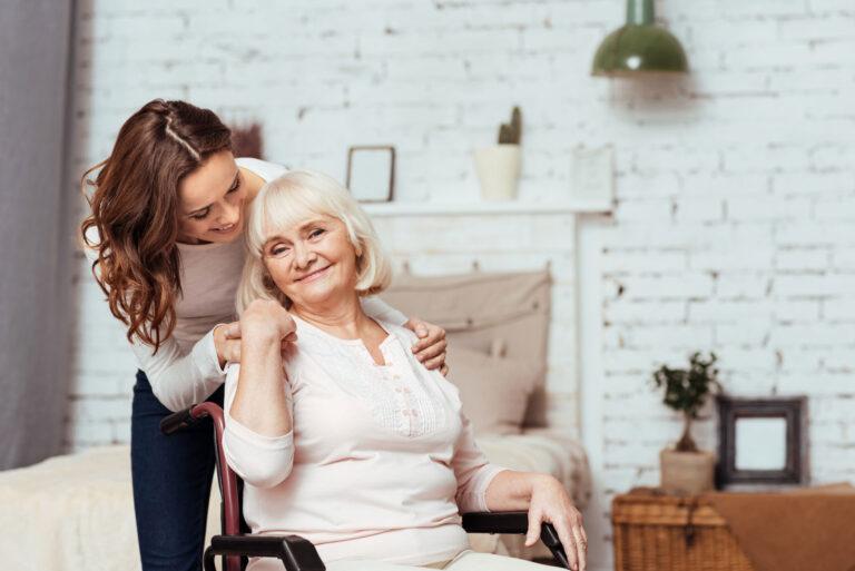Une jeune femme aide une dame âgée chez elle
