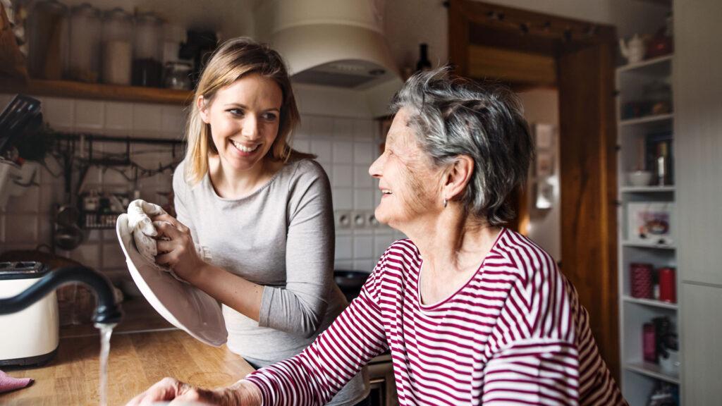 Une dame âgée se faisant aider par une jeune femme