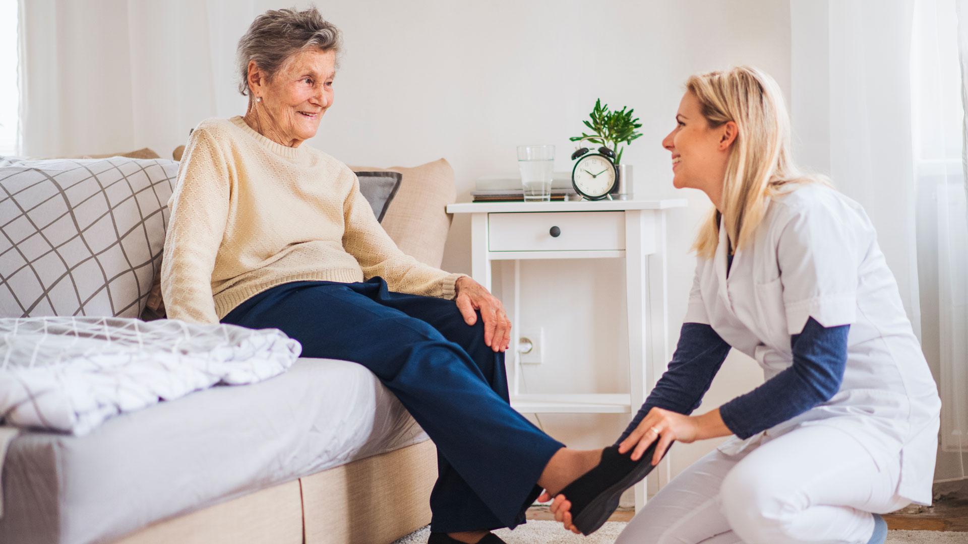 Une jeune femme aide une personne âgée à se chausser